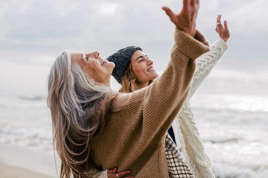 Senior woman and her daughter enjoying a winter day on the beach.