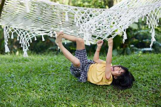 Asian children playing in a hammock on a background of green nature woods
