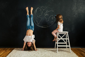 Children having fun in the room drawing on blackboard