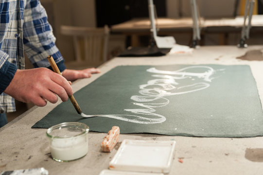 A Master Calligrapher writing using a special paintbrush