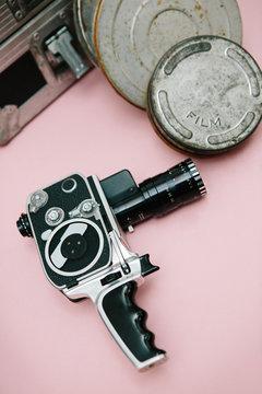Vintage cinema camera and film cans over pink background
