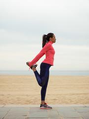 Flexible black woman stretching on beach