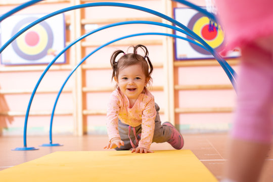 Baby girl crawling on mat in gym class. Lifestyle concept of children activity.