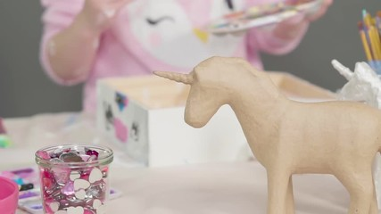 Wall Mural - Painting with a white acrylic paint unicorn paper mache figurine.