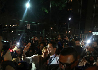 Venezuelan opposition leader Juan Guaido, who many nations have recognized as the country's rightful interim ruler, takes a picture with a supporter in Caracas