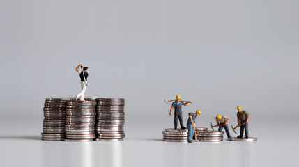 Miniature people standing on a pile of coins. A concept of income inequality. Fototapete