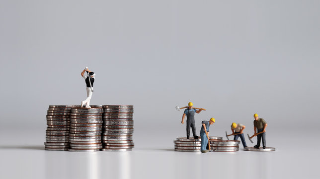 Miniature people standing on a pile of coins. A concept of income inequality.