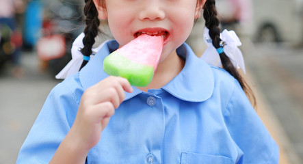 Close-up mouth of little girl in school uniform eating ice-cream.