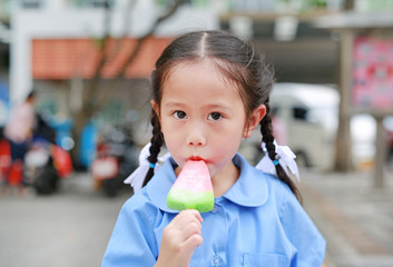 Adorable little Asian child girl in school uniform eating ice-cream in the park.