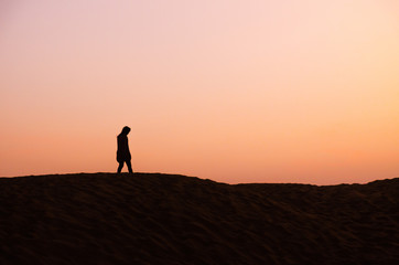 silhouette of lonely man in beautiful evening in desert