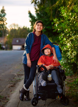 Sister standing next to disabled little brother in wheelchair outdoors