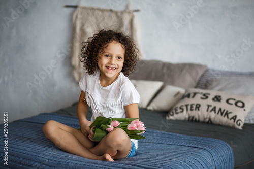 Happy mother's day, daughter gives a bouquet of tulips. African-American girl with a smile without teeth.