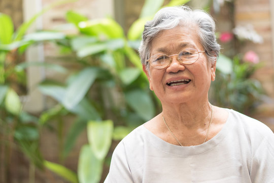 Happy senior society concept. Portrait of Asian female older ageing woman smiling with happiness in garden at home, nursing home, or wellbeing county