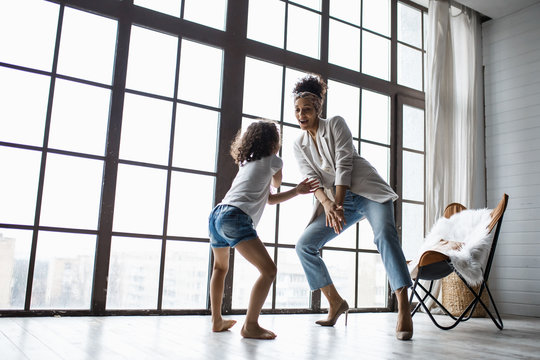 Happy loving afro american family. Young mother and her daughter playing in the nursery. Mom and daughter are dancing on the background of a large window