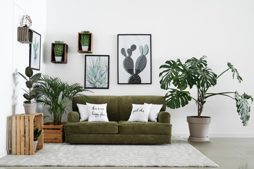 Interior of modern room with comfortable sofa and houseplants Fototapete