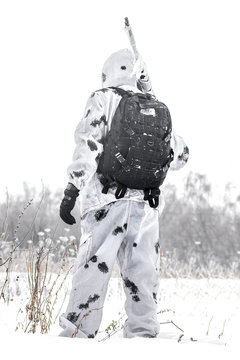 Man soldier in the winter on a hunt with a sniper rifle in white winter camouflage stay in the snow