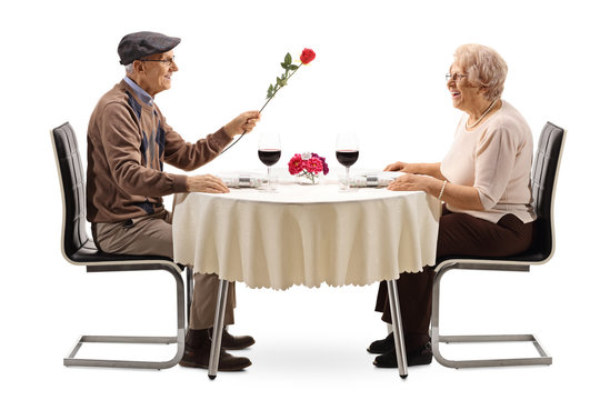 Senior man giving a red rose to a senior woman at a restaurant table