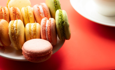 Pile of sweet and colourful french macaroons on red background.