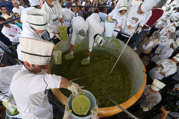 Volunteers from a culinary school mix mashed avocados as they attempt to set a new Guinness World Record for the largest serving of guacamole in Concepcion de Buenos Aires, Jalisco