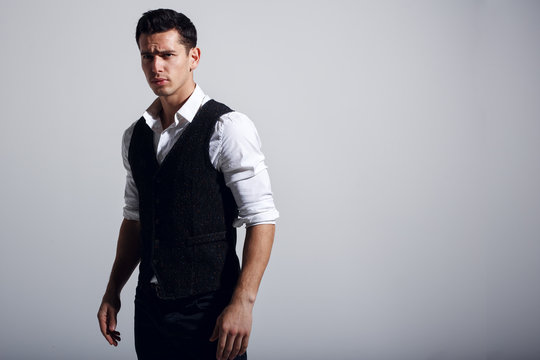 Young handsome man wearing white shirt, black vest, standing near grey wall. Studio portrait, isolated on gray background. Horizontzal view.