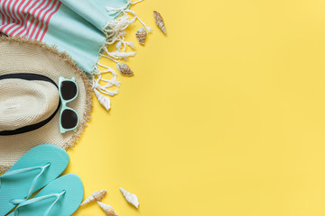 Outfit for beach and tropical vacations, straw sunhat, sun glasses on yellow. Summer.
