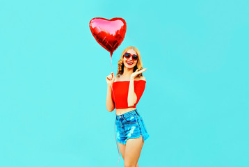 Portrait happy laughing surprised woman holding red heart shaped air balloon on colorful blue background