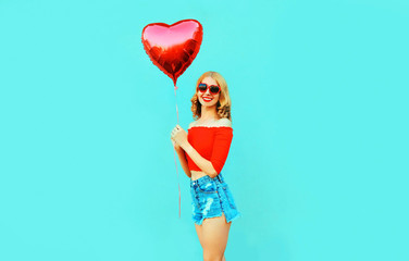 Portrait cute happy smiling woman in shorts holding red heart shaped air balloon on colorful blue background