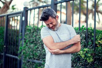 Man feeling elbow pain on the street