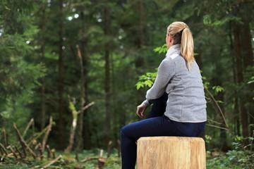 Frau sitzt zufrieden im Wald