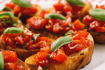 Tasty savory tomato Italian appetizers, or bruschetta, on slices of toasted baguette garnished with basil, close up