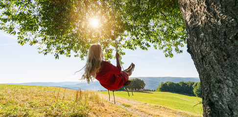 Unrecognizable girl in white dress swaying on a tree swing on peaceful evening. Lady sitting on a wooden swing and looking at golden sunset. Young woman swinging at sunrise Wall mural