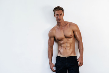 Portrait of sexy athletic man in black pants with naked torso on white background