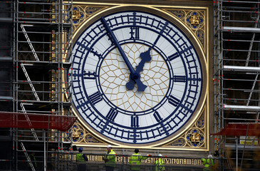 Workers stand next to the newly uncovered clock face of Big Ben in London