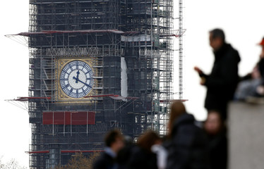 People stand near Big Ben with its newly uncovered clock face, in London