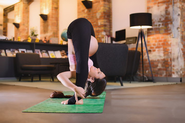 Young pregnant woman practicing yoga