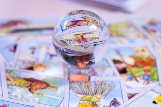 The crystal ball of predictions stands on the background of tarot cards. Blurred card background