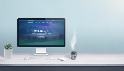 Web design studio with computer display, keyboard and mouse on office work desk. Modern flat design web page on display. Copy space beside.