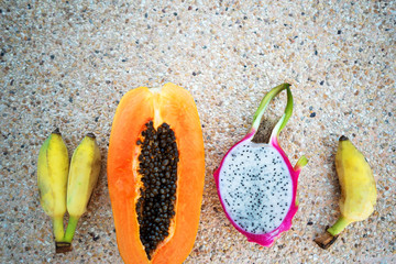 tropical fruits lie on the sand background