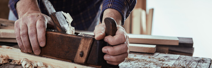 Panorama banner of a carpenter planing wood