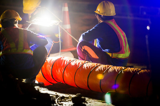 selective focus to spotlight and construction worker is working at night in construction site