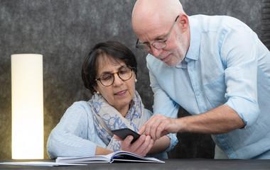 happy senior couple reading message to smartphone