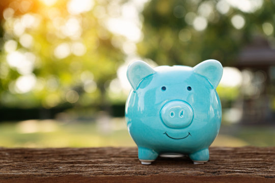 Blue piggy bank on wooden table over blurred green bokeh background. Saving money concept
