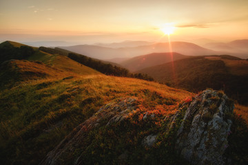 Sunset in the mountains with warm light and beautiful view to mountains in the fog. Ukraine, Carpathians Borjava Ridge