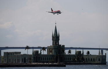 An airplane of Avianca flies over the Ilha Fiscal, an island in Guanabara Bay, as it prepares to land at Santos Dumont airport in Rio de Janeiro