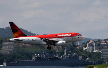 An Airbus A318 airplane of Avianca Brazil flies over the Guanabara Bay as it prepares to land at Santos Dumont airport in Rio de Janeiro