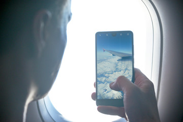 A passenger on the phone photographs in the plane