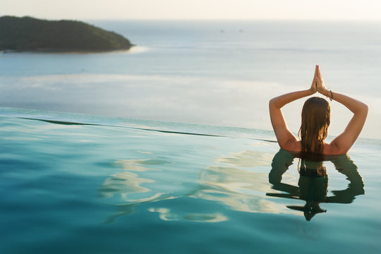 girl in the pool at sunset doing yoga with a view of the mountains and the sea