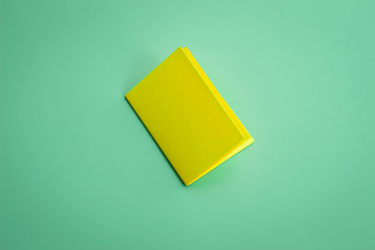 Blank portrait mock-up paper. Yellow brochure magazine isolated on green , changeable background.