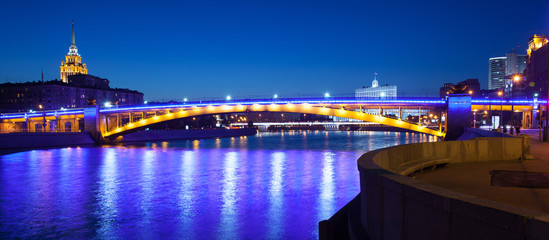 panorama of Moscow city with lighting Smolensky bridge and river at summer evening
