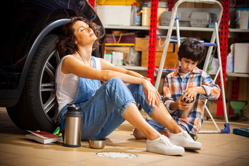 resting mechanic woman and boy with thermos